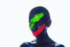 有黑油漆的女孩在面孔 绿色红色 免版税库存图片