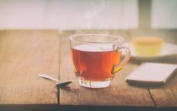 有黄油蛋糕的热的在桌上的茶杯和smartpho在wi 免版税图库摄影