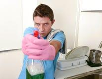 有洗涤剂浪花的厨房装瓶的年轻懒惰房子擦净剂人洗涤物和清洁 免版税库存图片