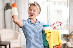 有洗涤剂的妇女干净的房子的 图库摄影