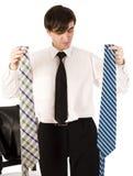 有年轻深色的英俊的人在白色背景隔绝的两条领带之间的选择,生活方式商人 库存图片