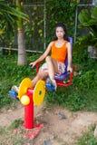 有锻炼机器的亚裔泰国女孩在公园 免版税图库摄影
