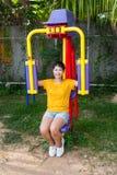 有锻炼机器的亚裔泰国女孩在公园 库存照片