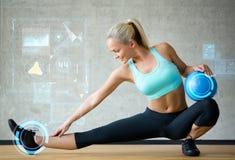 有锻炼球的微笑的妇女在健身房 库存照片