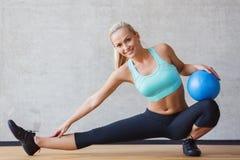 有锻炼球的微笑的妇女在健身房 免版税库存照片