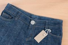 有价牌的蓝色牛仔裤在木背景 库存照片