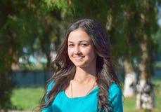 有暴牙的微笑和棕色头发的女孩在一件绿色礼服 免版税图库摄影