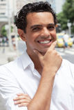 有暴牙的微笑的英俊的拉丁人在城市 免版税库存照片