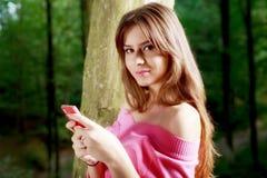 有暴牙的微笑的年轻美丽的妇女传送信息 库存照片