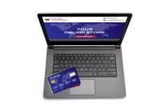 有购物网站的膝上型计算机屏幕和在键盘的信用卡 库存图片