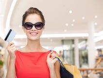 有购物袋和信用卡的微笑的妇女 图库摄影