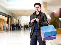 有购物袋和信用卡的微笑的英俊的人 免版税图库摄影