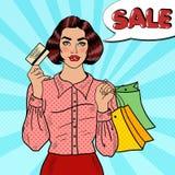 有购物袋和信用卡的流行艺术愉快的妇女 用在白色背景的戴西装饰的季节性sale.green标签 免版税库存图片