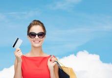 有购物袋和塑料卡片的微笑的妇女 免版税库存图片