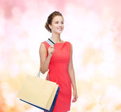有购物袋和塑料卡片的微笑的妇女 免版税库存照片