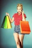 有购物袋和手机减速火箭的样式的女孩 免版税库存图片