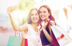 有购物袋和智能手机的愉快的妇女 图库摄影