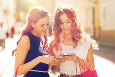 有购物袋和智能手机的愉快的妇女 库存照片
