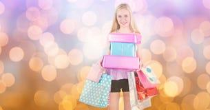 有购物袋和礼物的妇女在迷离背景 免版税库存照片