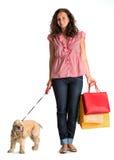 有购物袋和美国西班牙猎狗的卷曲妇女 免版税库存图片