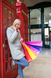 有购物袋的一名美丽的妇女在购物街道,伦敦 图库摄影