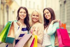 有购物袋的三个微笑的女孩在ctiy 图库摄影