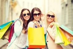 有购物袋的三个微笑的女孩在ctiy 免版税图库摄影