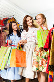 有购物袋的三名微笑的妇女在商店 库存照片