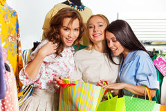 有购物袋的三名年轻激动的妇女 免版税库存照片