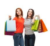 有购物袋的两个微笑的十几岁的女孩 库存图片