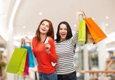 有购物袋的两个微笑的十几岁的女孩 库存照片