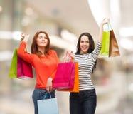 有购物袋的两个微笑的十几岁的女孩 免版税库存图片