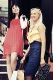 有购物袋的两名愉快的年轻时尚妇女 免版税库存照片
