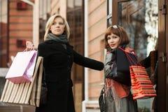 有购物袋的两名年轻时尚妇女在购物中心门 免版税库存图片