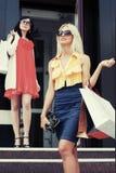 有购物袋的两名年轻时尚妇女在购物中心 免版税库存照片