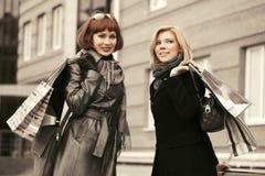 有购物袋的两名年轻时尚妇女走在城市街道的 图库摄影