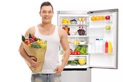 有购物袋的人在一个开放冰箱前面 库存图片