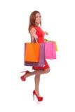 有购物袋的女孩。快乐的少妇全长侧视图微笑红色的礼服的拿着购物袋和,当standi时 免版税库存照片