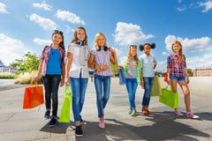 有购物袋的女孩一起走在路的 免版税库存照片