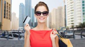 有购物袋的妇女和在城市的信用卡 免版税库存照片