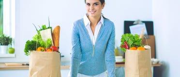 有购物袋的妇女在家厨房里,站立近的书桌 免版税库存照片
