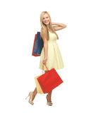 有购物袋的妇女在礼服和高跟鞋 免版税库存照片