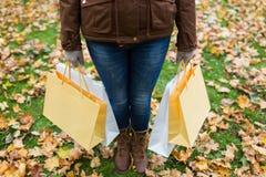 有购物袋的妇女在秋天公园 免版税库存照片