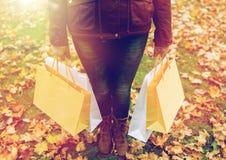 有购物袋的妇女在秋天公园 库存图片