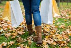 有购物袋的妇女走沿秋天公园的 库存照片