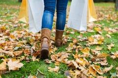 有购物袋的妇女走沿秋天公园的 免版税库存照片