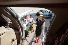 有购物袋的富有的妇女上私人喷气式飞机的 免版税库存图片