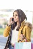 有购物袋的幸福美丽的拉丁妇女谈话由酸碱度 免版税库存图片