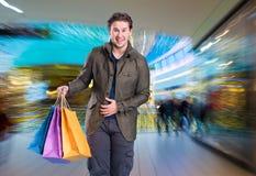 有购物袋的微笑的英俊的人 免版税库存照片