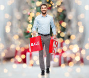 有购物袋的愉快的人在圣诞灯 免版税库存照片
